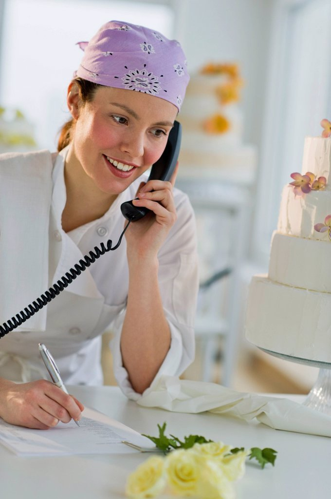 Happy young woman taking order near wedding cake : Stock Photo