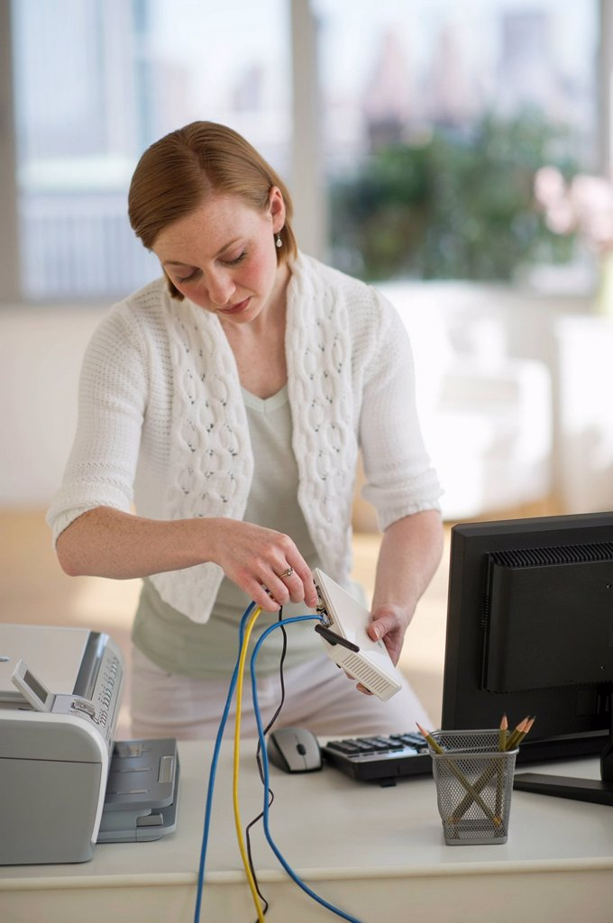 Stock Photo: 1795R-44501 USA, New Jersey, Jersey City, woman installing router at home office