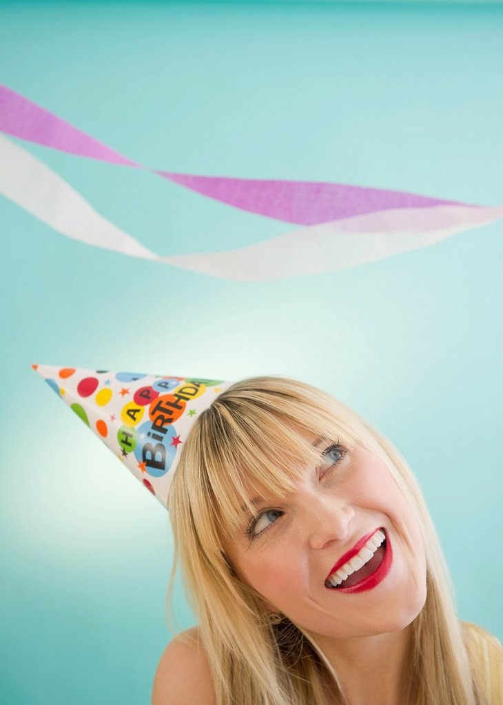 Young woman wearing party hat laughing : Stock Photo