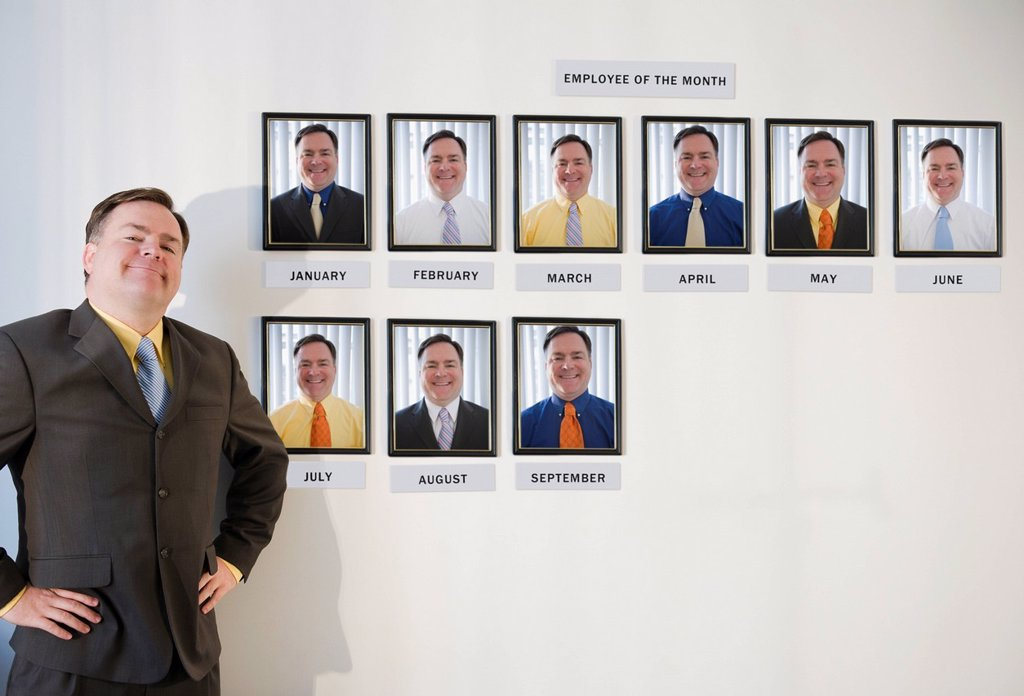 USA, Jersey City, New Jersey, businessman standing in front of employee of the month portraits : Stock Photo
