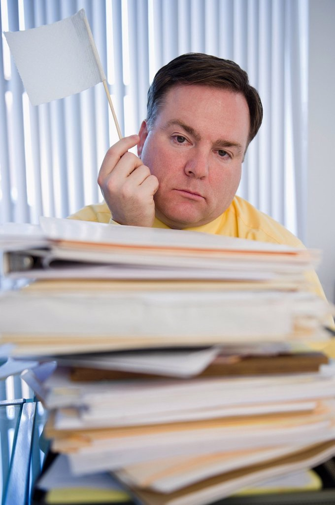 USA, Jersey City, New Jersey, businessman holding white flag over stack of paperwork : Stock Photo