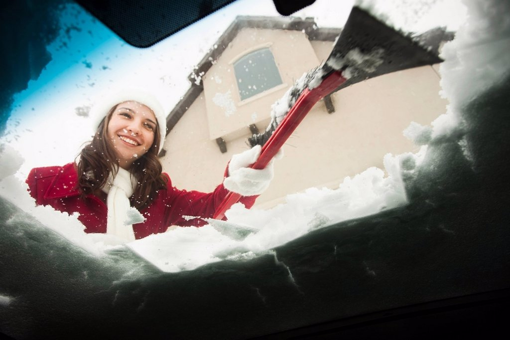 USA, Utah, Lehi, Young woman scraping snow from car windscreen : Stock Photo