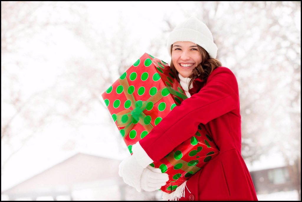 Stock Photo: 1795R-46068 USA, Utah, Lehi, Portrait of young woman hugging Christmas gift outdoors