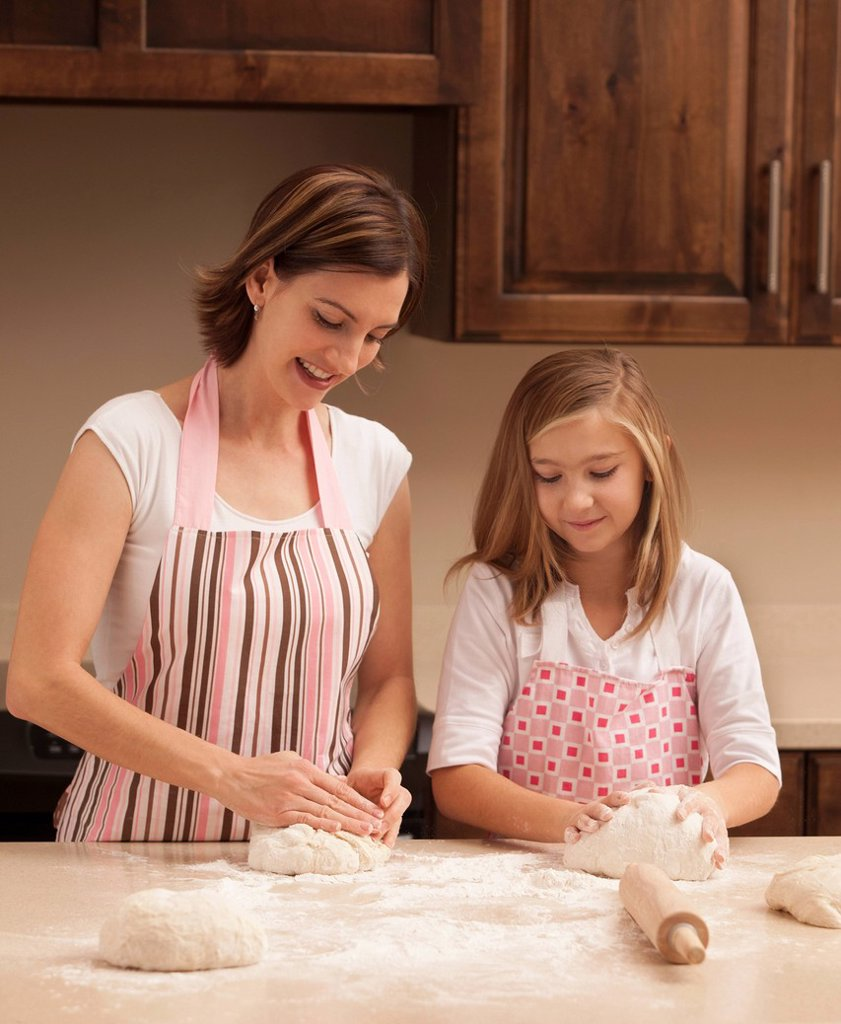 Mother and daughter 10_11 kneading dough in kitchen : Stock Photo