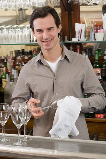 Male bartender drying wine glasses : Stock Photo