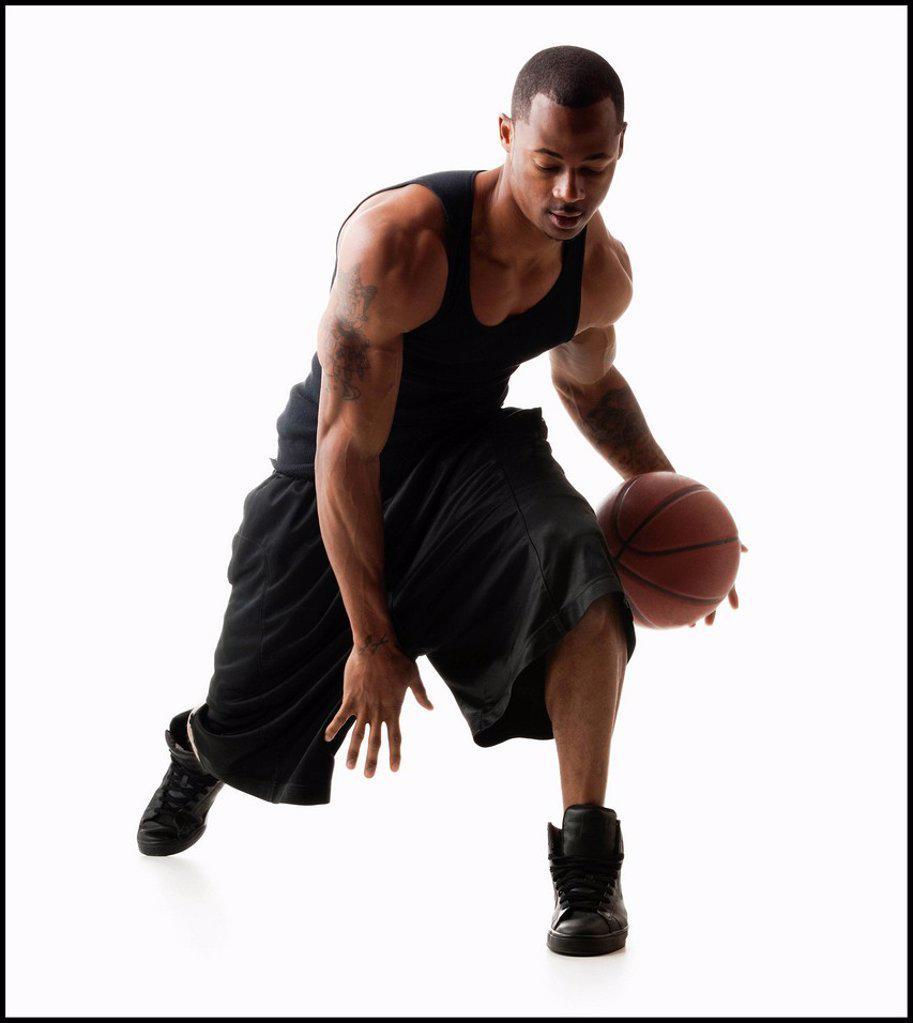 Studio shot of man playing basketball : Stock Photo