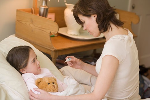 Stock Photo: 1795R-4682 Mother checking young daughter's temperature with thermometer