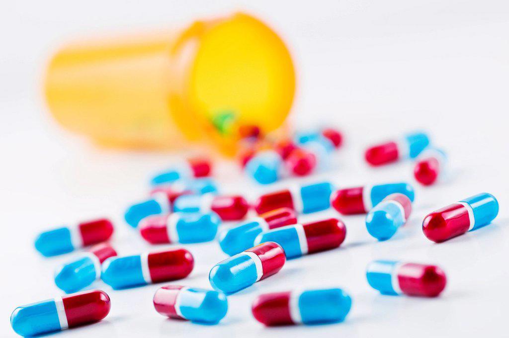 Stock Photo: 1795R-46876 Studio shot of capsules spilling from bottle
