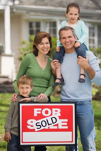 Family in front of house with For Sale/Sold sign : Stock Photo
