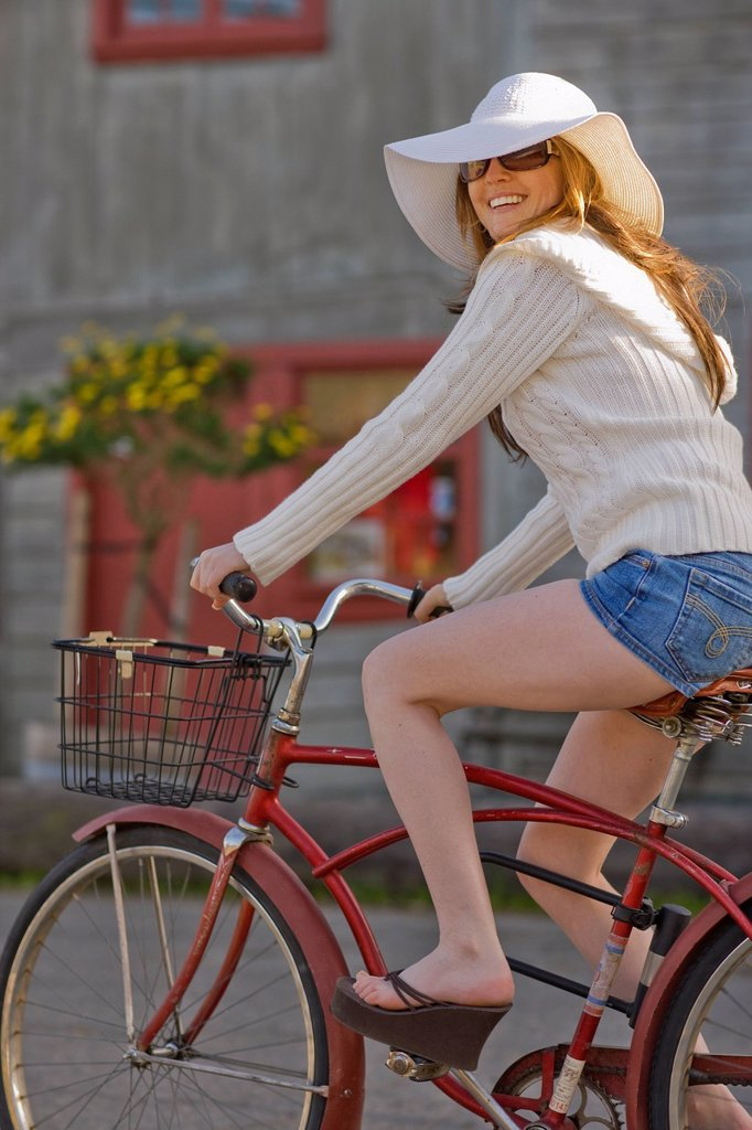 USA, California, Bolinas, Young woman riding bicycle in street : Stock Photo