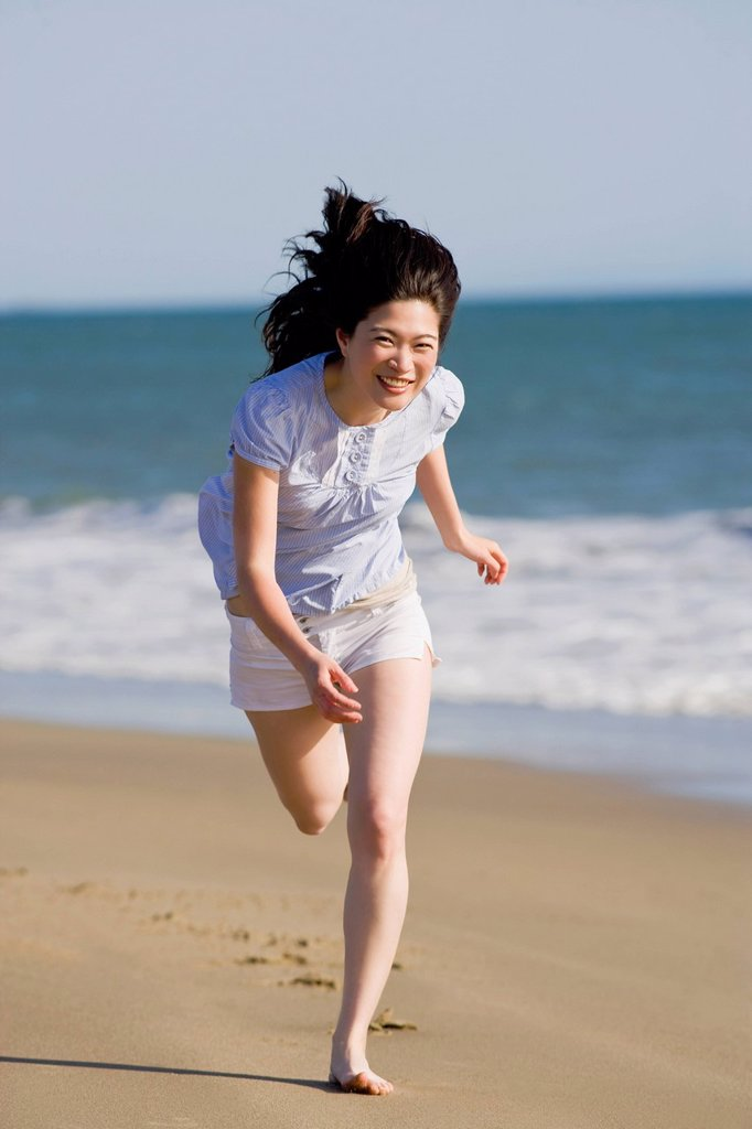 Stock Photo: 1795R-47297 USA, California, Point Reyes, Young woman running on beach