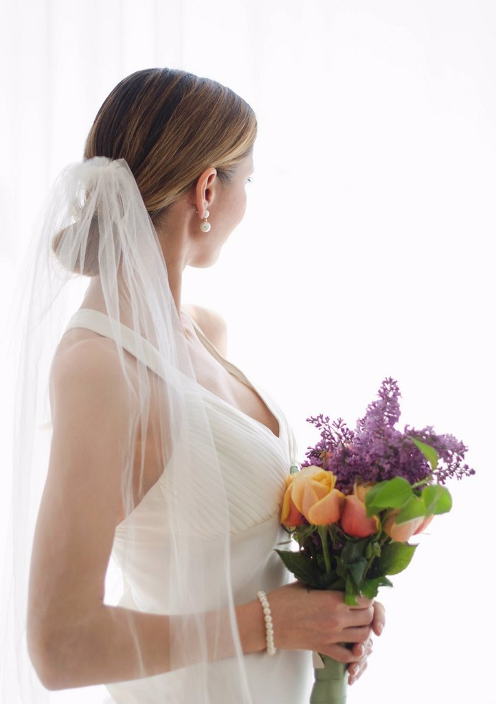 Bride holding floral bouquet : Stock Photo