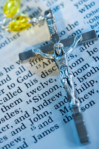Close up of crucifix with rosary on Bible : Stock Photo