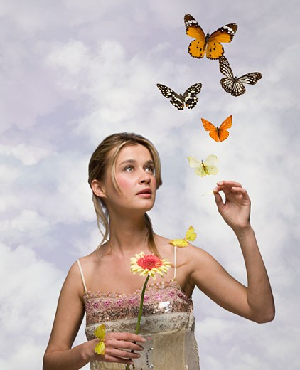 Stock Photo: 1795R-4874 Young woman with flower and butterflies