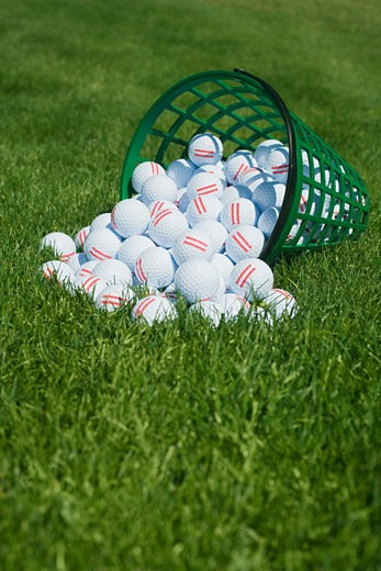 Stock Photo: 1795R-4907 Basket of golf balls spilling onto grass