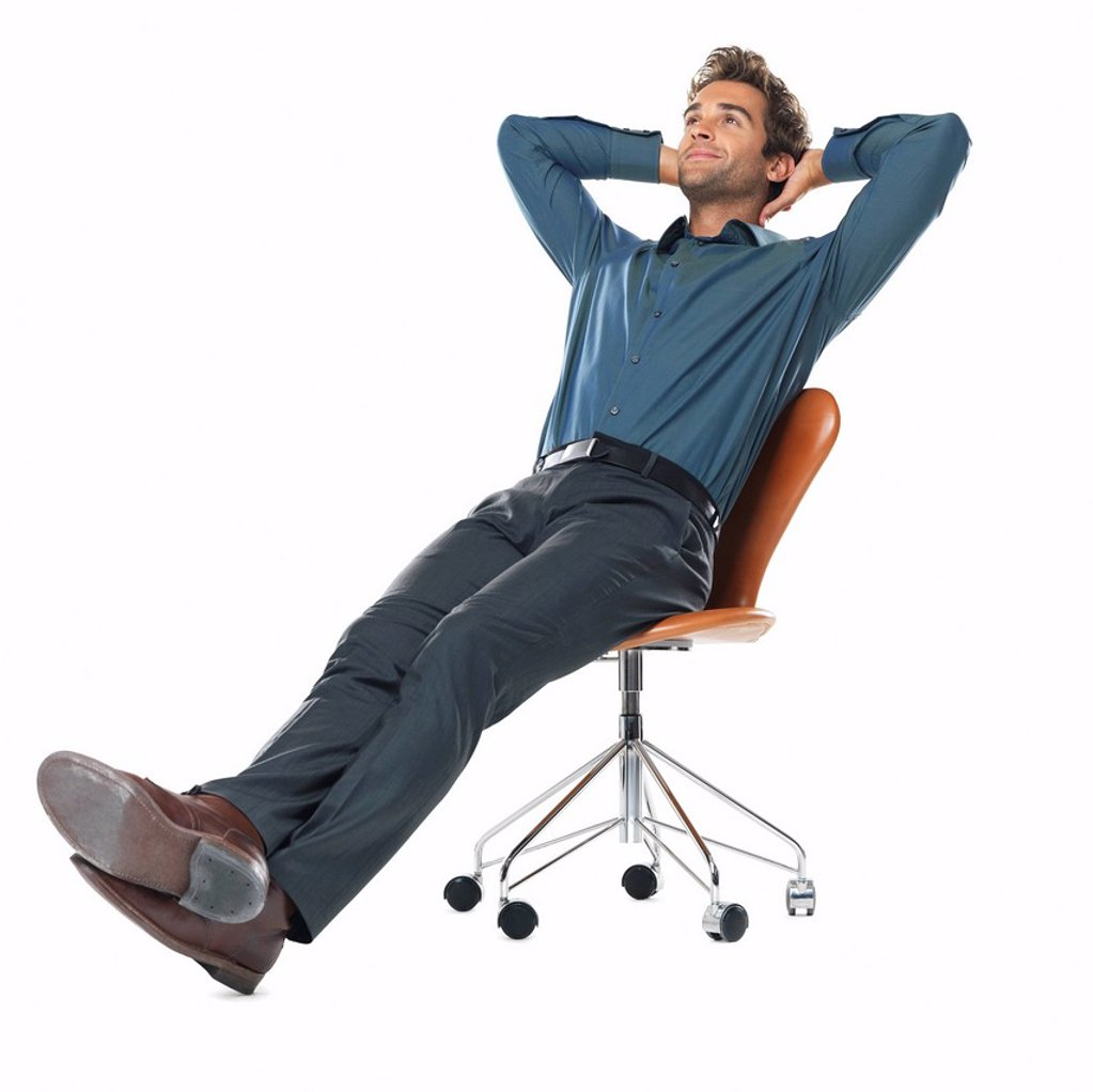 Studio shot of young business man relaxing on chair with hands behind head : Stock Photo