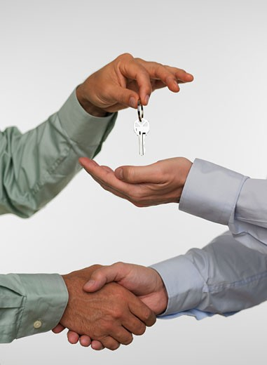 Two men closing deal and handing over keys : Stock Photo