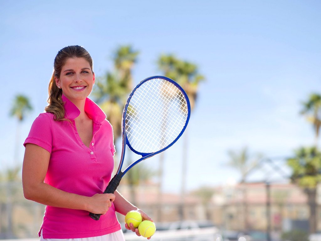 Young woman with tennis balls and racket : Stock Photo
