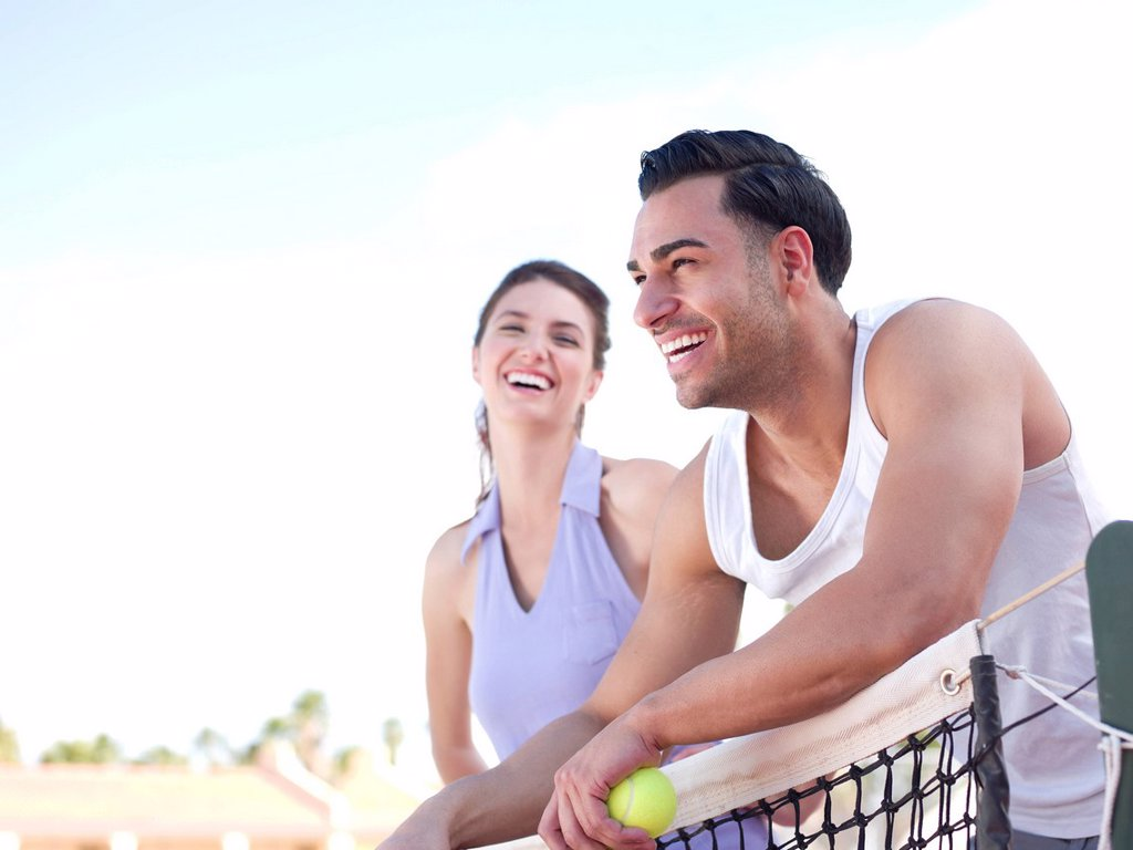 Stock Photo: 1795R-50394 Smiling couple standing near tennis net