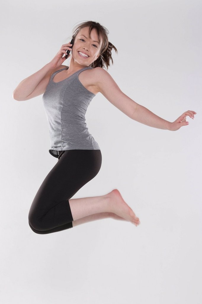 Portrait of young woman jumping, studio shot : Stock Photo