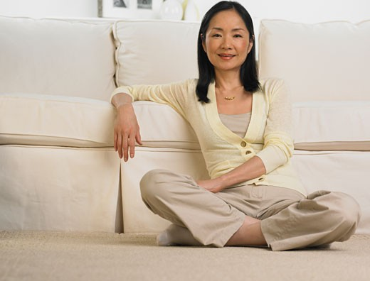 Middle-aged Asian woman leaning on sofa smiling : Stock Photo