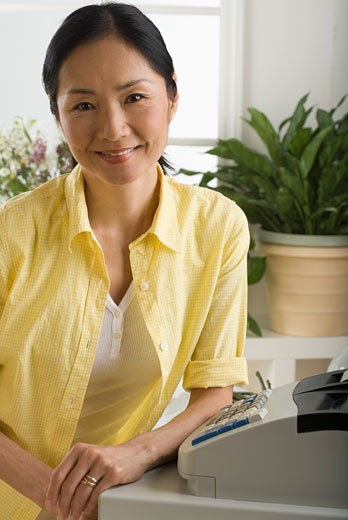Asian woman smiling and leaning on cash register : Stock Photo
