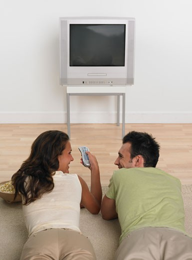 Couple laying on floor with popcorn watching television  : Stock Photo