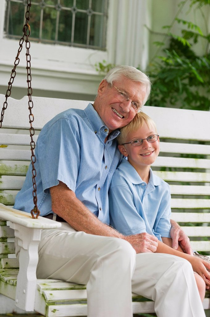 Stock Photo: 1795R-54598 Grandfather and grandson 10_11 sitting on porch swing