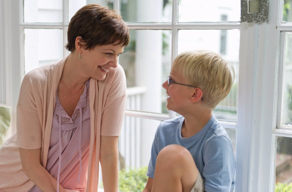 Stock Photo: 1795R-54652 Mother and son 10_11 sitting in front of window