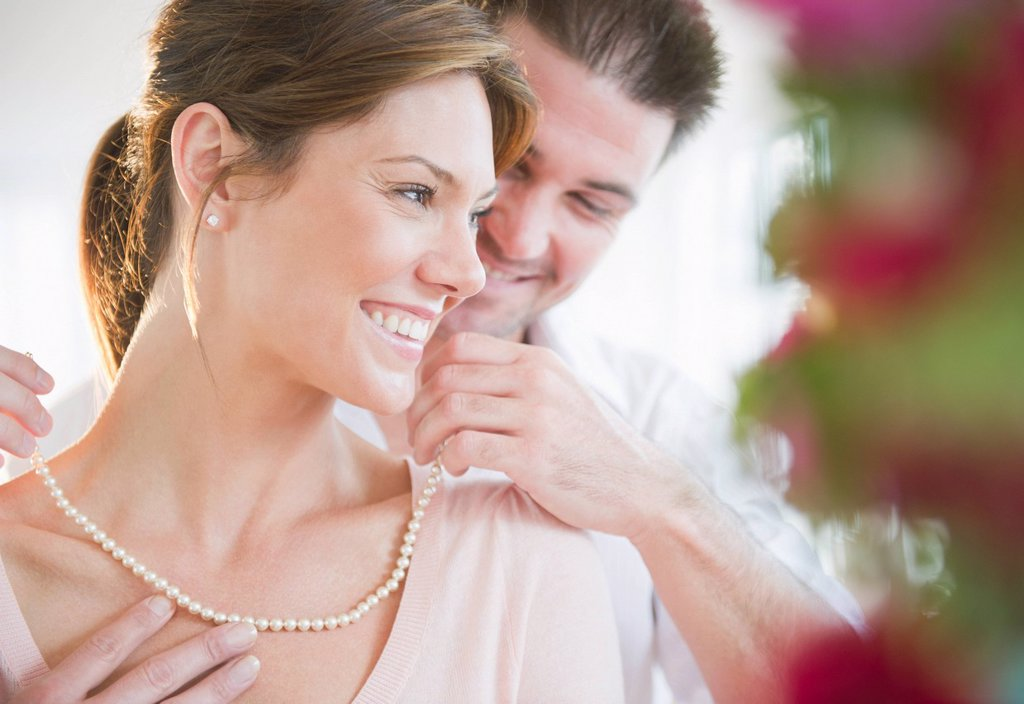 Manputting pearls on hisgirlfriend´s neck : Stock Photo