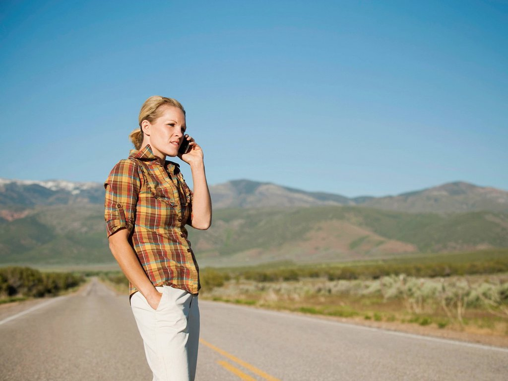 Stock Photo: 1795R-55413 USA, Utah, Kanosh, Mid adult woman calling emergency services on empty desert road