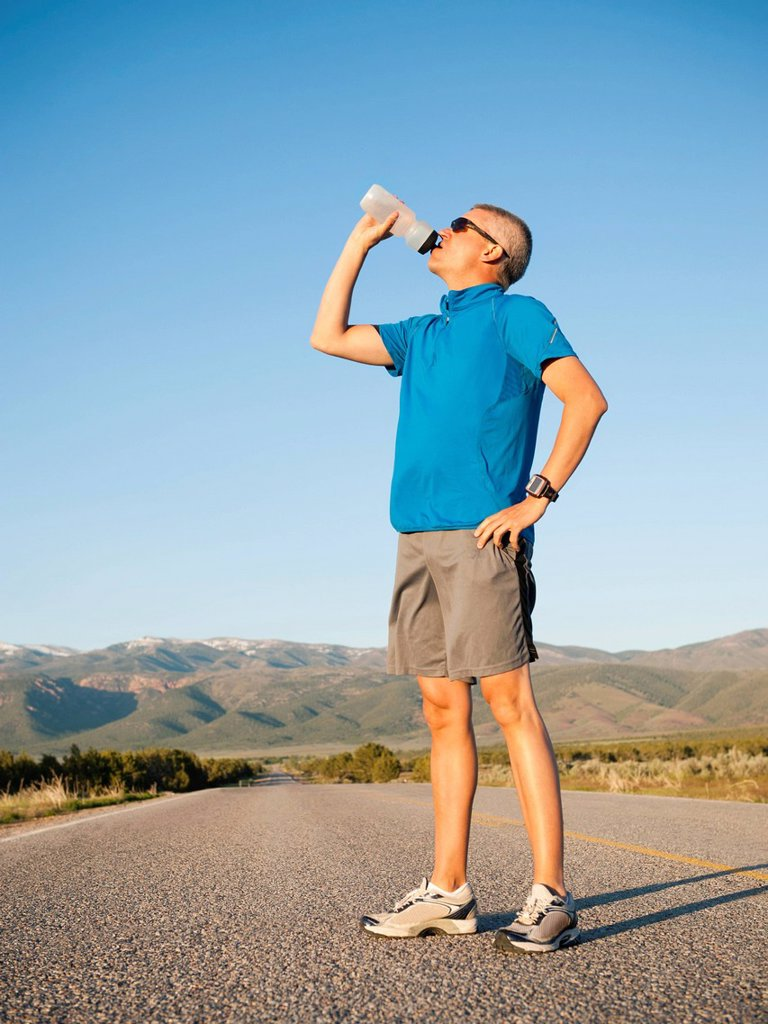 Stock Photo: 1795R-55432 Mid adult an drinking water while taking break from running on empty road
