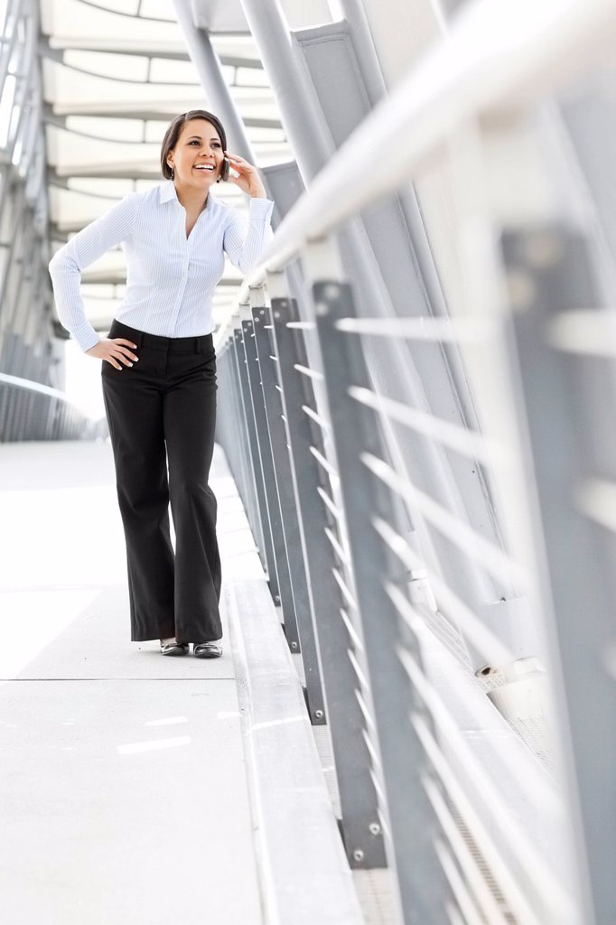 Young businesswoman on walkway, using cell phone : Stock Photo