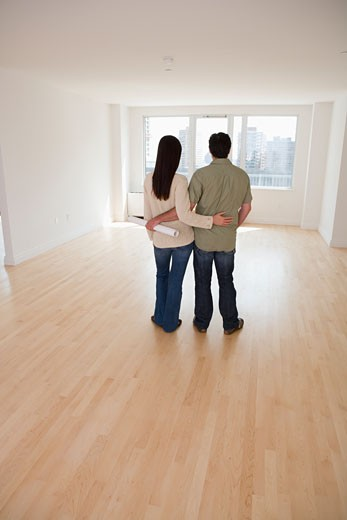 Rear view of couple with blueprints in empty room : Stock Photo