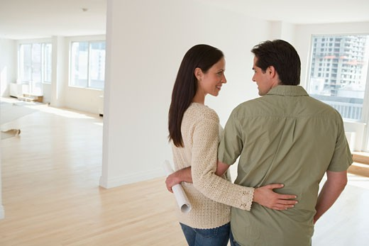 Couple hugging and holding blueprints in empty house : Stock Photo