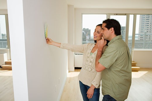 Couple holding paint swatches up to wall : Stock Photo