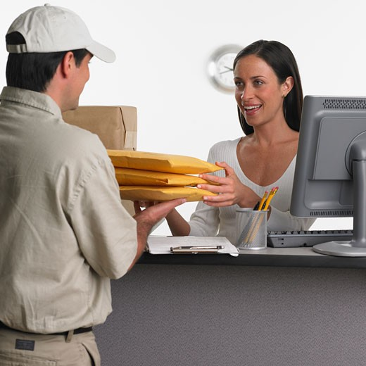 Woman behind counter receiving delivery : Stock Photo