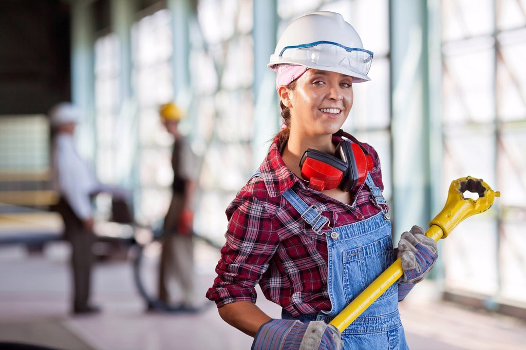 Portrait of female manual worker wearing hardhat : Stock Photo