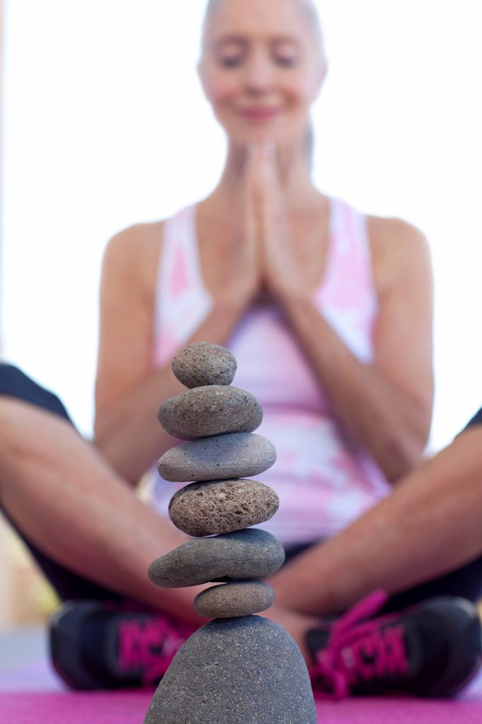 Woman doing yoga behind stack of pebbles : Stock Photo
