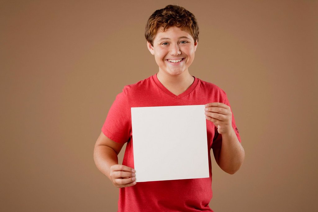 Stock Photo: 1795R-56392 Studio portrait of boy 12_13 holding blank sheet of paper