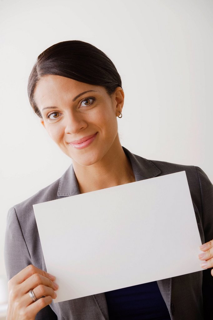 Smiling businesswoman holing blank page, studio shot : Stock Photo