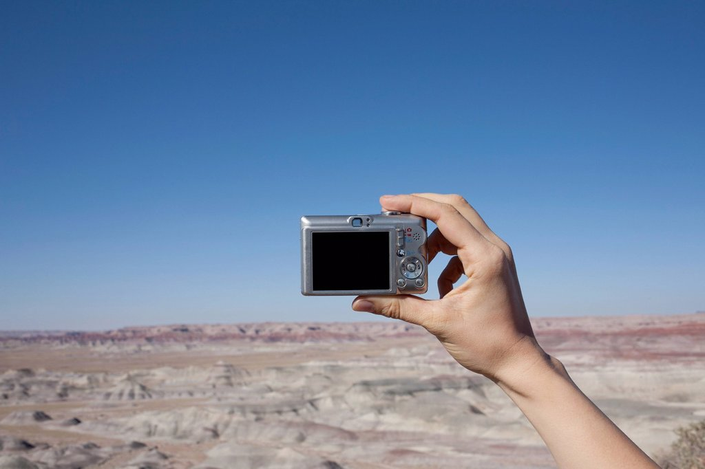 Hand of woman holding camera up against blue sky : Stock Photo