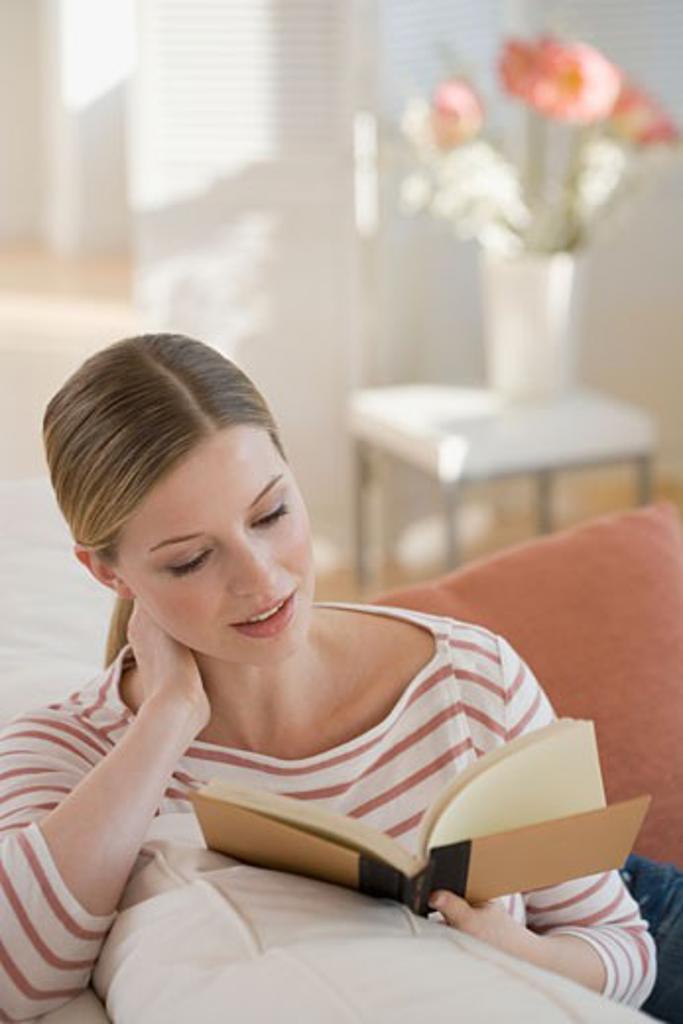 Woman reading on sofa : Stock Photo