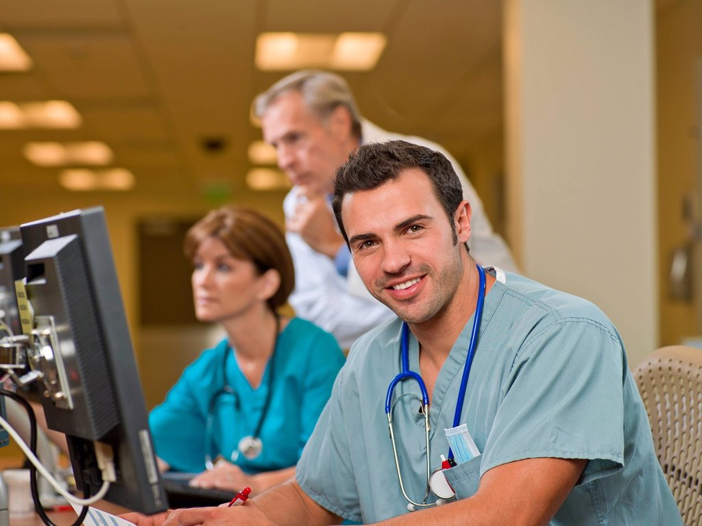 Doctor and surgeons working on computers in hospital : Stock Photo