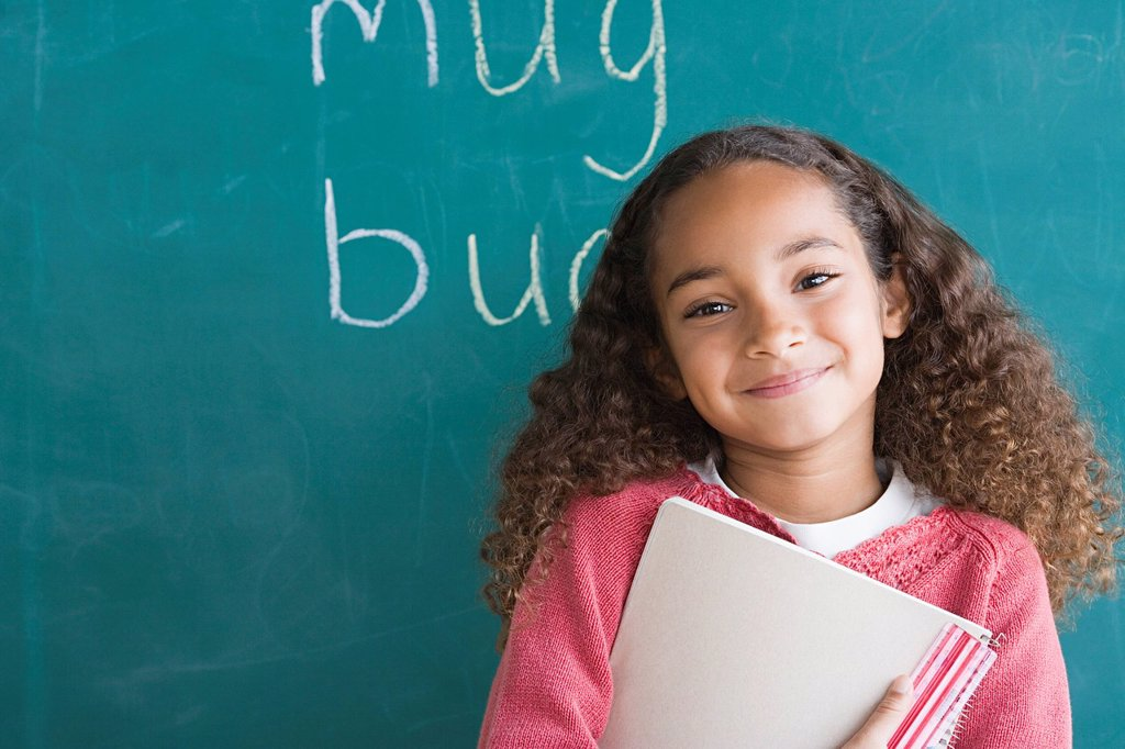 Smiling girl 6_7 against blackboard : Stock Photo