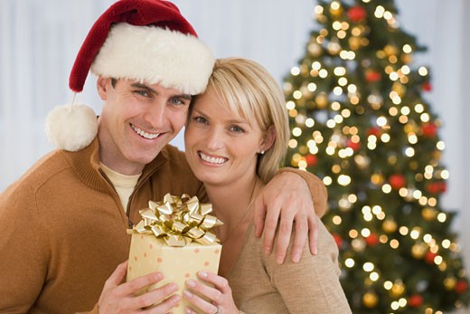 Portrait of couple holding Christmas gift : Stock Photo