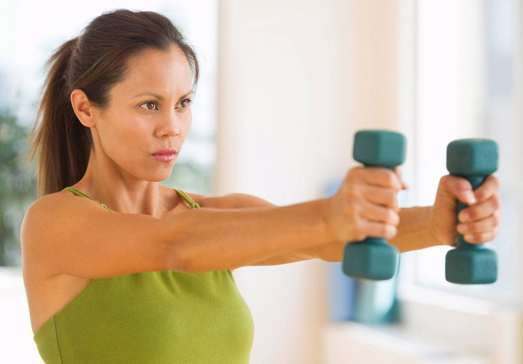 Mid adult woman training with dumbbell : Stock Photo