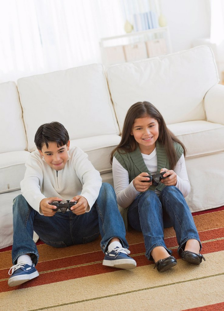 Stock Photo: 1795R-58640 Brother (12-13) and sister (10-11) playing video games