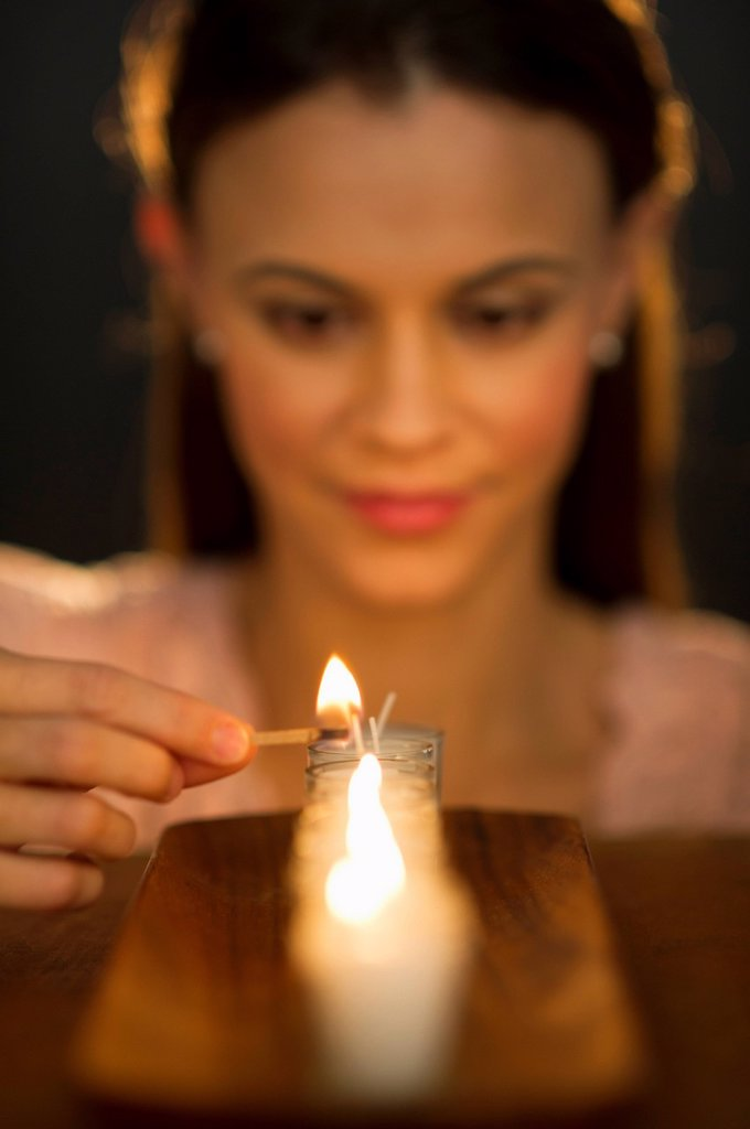 Stock Photo: 1795R-58774 Woman igniting candle