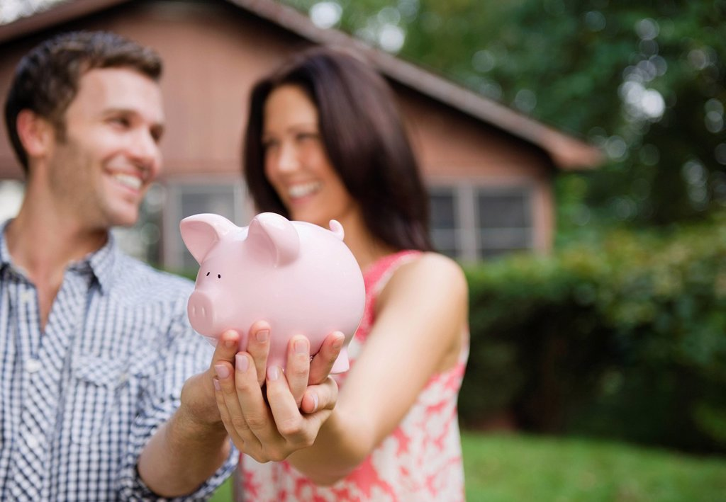 Stock Photo: 1795R-59062 USA, New York, Putnam Valley, Roaring Brook Lake, Couple holding piggy bank